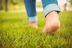 Niedriger Abschnitt der Frau gehend auf Gras Stockfotos