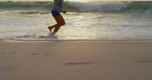 Niedriger Abschnitt der Frau spielend mit Meereswellen auf dem Strand 4k stock video footage