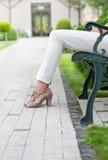 Niedriger Abschnitt der jungen Frau entspannend auf Parkbank Stockfotografie