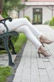 Niedriger Abschnitt der jungen Frau mit den hohen Absätzen, die auf Parkbank sitzen Lizenzfreie Stockfotos
