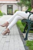 Niedriger Abschnitt der jungen Frau mit den hohen Absätzen, die auf Parkbank sitzen Lizenzfreies Stockbild