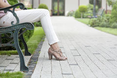 Niedriger Abschnitt der jungen Frau sitzend auf Parkbank Stockbilder