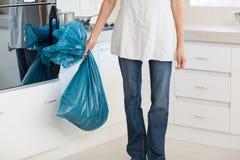 Niedriger Abschnitt der tragenden Abfalltasche der Frau in der Küche Stockfotos