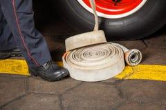 Niedriger Abschnitt des Feuerwehrmanns Standing By Hose Lizenzfreie Stockbilder