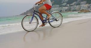 Niedriger Abschnitt des Mannes Fahrrad auf den Strand 4k fahrend stock video