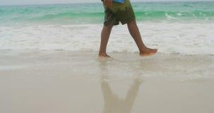 Niedriger Abschnitt des Mannes spielend mit Gischt auf dem Strand 4k stock footage
