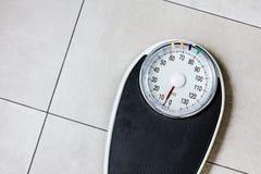 Niedriger Abschnitt des Mannes stehend auf Gewichtsskala lizenzfreie stockfotos