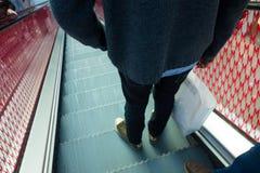 Niedriger Abschnitt eines Mannes, der eine Einkaufstasche in bewegliche Treppe hält Lizenzfreie Stockfotos