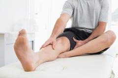 Niedriger Abschnitt eines Mannes mit den Händen auf einem schmerzlichen Bein Stockfoto