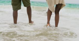 Niedriger Abschnitt von den Afroamerikanerpaaren, die mit Meereswellen auf dem Strand 4k spielen stock video