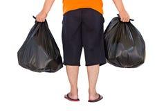 Niedriger Abschnitt von den tragenden Abfalltaschen des jungen Mannes lokalisiert auf Weiß Lizenzfreie Stockfotografie