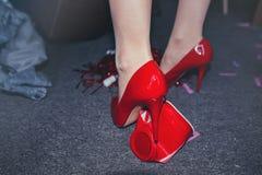 Niedriger Abschnitt von Frau ` s Beinen in den roten Fersen im unordentlichen Raum Lizenzfreies Stockfoto