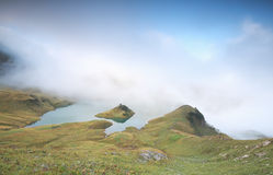Niedriger Nebel über alpinem See am Morgen stockbilder