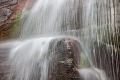 Niedriger Vorhang des Wasserfalls und unscharfes Bewegungswasser, die hinunter die vertikale rote Klippe strömt Stockbild