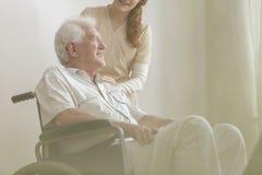 Niedriger Winkel auf dem Lächeln und glücklicher behinderter älterer Mann in einem wheelch lizenzfreies stockbild