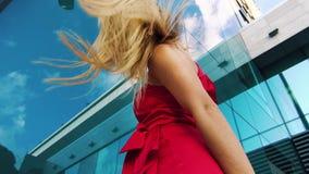 Niedriger Winkel blonder Dame im roten Tanzen gegen die Spiegelwand, die blauen Himmel reflektiert stock video footage