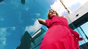 Niedriger Winkel blonder Dame im roten Tanzen gegen reflektierenden Himmel der Glasoberfläche stock footage