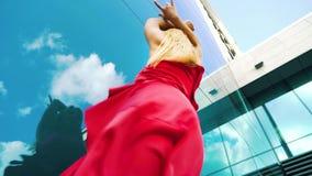 Niedriger Winkel des sexy Blondinetanzens gegen reflektierenden Himmel des Glasgebäudes stock video footage