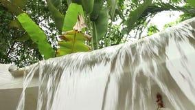 Niedriger Winkel mittleres CU eines kleinen künstlichen Wasserfalls in tropischem Südostasien stock video