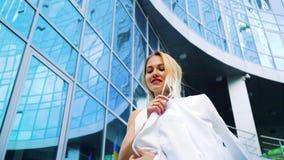 Niedriger Winkel von stilvollen Blondinen überschreiten durch modernes Gebäude in der Zeitlupe stock video footage