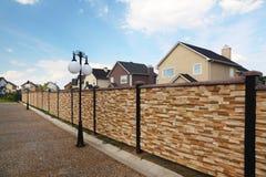 Niedriger Zaun und Laternen auf Hintergrund der Häuschen Lizenzfreies Stockfoto
