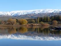 Śnieg zakrywał pasmo górskie odbijającego w jeziorze przy masarki tamą, Środkowy Otago, Nowa Zelandia Obrazy Royalty Free