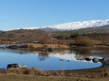 Śnieg zakrywał pasmo górskie odbijającego w jeziorze przy masarki tamą, Środkowy Otago, Nowa Zelandia Zdjęcie Royalty Free