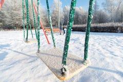 Śnieg zakrywający obruszenie przy boiskiem i huśtawka wewnątrz Fotografia Stock