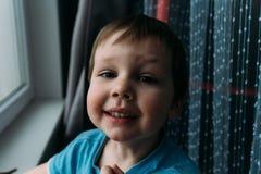 Niegrzeczna chłopiec ono uśmiecha się przy kamerą, portret dziecko obraz stock