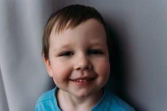 Niegrzeczna ch?opiec ono u?miecha si? przy kamer?, portret dziecko fotografia royalty free