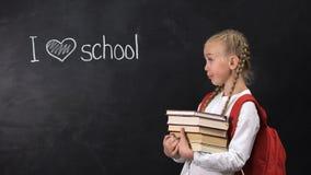 Niegrzeczna uczennica stoi blisko blackboard z książkami, kocham szkoły pisać zbiory