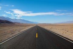 Niekończący się i osamotniona blacktop droga iść w pasmo górskie wchodzić do Śmiertelnego Dolinnego parka narodowego fotografia royalty free