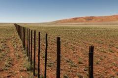 Niekończący się ogrodzenie w pustynia krajobrazie Zdjęcia Royalty Free