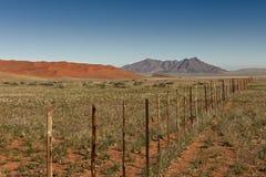 Niekończący się ogrodzenie w pustynia krajobrazie Zdjęcie Royalty Free