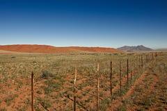 Niekończący się ogrodzenie w pustynia krajobrazie Obraz Stock
