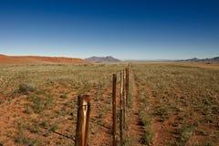 Niekończący się ogrodzenie w pustynia krajobrazie Fotografia Stock