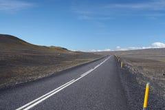 Niekończący się prosta asfaltowa droga w jałowym szerokim krajobrazie z żółtymi pobocze markierami w nigdzie, Iceland zdjęcie stock