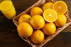 Niektóre pomarańcze w koszu na drewnianym tle obrazy stock