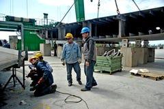 Niektóre pracownicy pracuje przy stocznią między dużymi żurawiami dla budowy mega jacht Fotografia Royalty Free