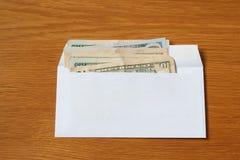 Niektóre USA dolarów banknoty w białej czarnej kopercie dla łapówki w biurze przy stołem fotografia stock