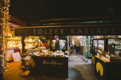 Niemcy, Monachium Grudzień 27, 2017: Bożenarodzeniowy jarmark, A mężczyzna sprzedawania sera stojaki przy kontuarem w zima wieczó Zdjęcia Royalty Free