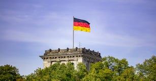 Niemiec chorągwiany falowanie na srebnym flagpole, Reichstag budynek w Berlin błękit nieba chmury tła obrazy royalty free
