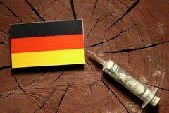 Niemiec flaga na fiszorku z strzykawki wstrzykiwania pieniądze Obraz Royalty Free