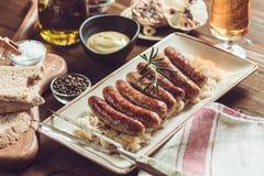 Niemiec Piec na grillu kiełbasy z Kapuścianą sałatką, musztardą i piwem, zdjęcie stock
