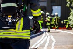 Niemieccy palacza Feuerwehr stojaki blisko wypadku zdjęcie stock