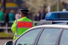 Niemieccy samochodu policyjnego i policjanta stojaki na ulicie Zdjęcie Stock