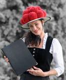 Niemiecka kelnerka trzyma menu jest ubranym bollenhut zdjęcia royalty free