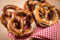 Niemiecki miękki Brezel precel z solą, szczypiorkami i masłem w chlebowym koszu, fotografia stock