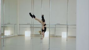 Niemożliwie słupa tancerz robi rozłamowi na pilonie w studiu podczas gdy zrozumienia do góry nogami Zdjęcie Royalty Free