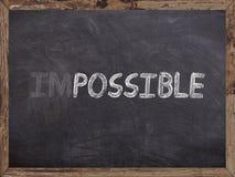 Niemożliwy wymazuje w ewentualnym writed na blackboard z drewnianym Fotografia Stock